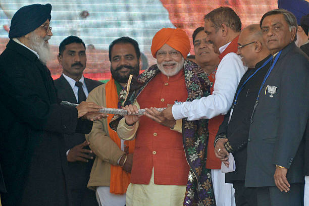 Indian Prime Minister Narendra Modi holds a sword presented by Punjab Chief Minister Parkash Singh Badal during the Bharatiya Janata Party rally at...