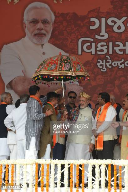 Indian Prime Minister Narendra Modi holds a traditional umbrella on his arrival to address a political rally at Surendranagar some 130 kms from...