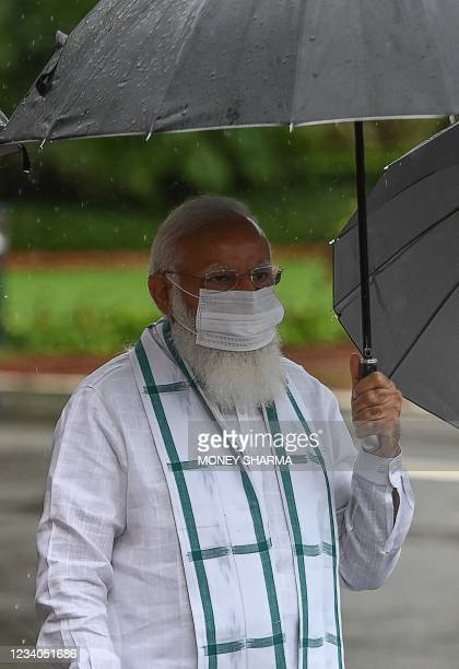 Indian Prime Minister Narendra Modi holds an umbrella during a rainfall as he arrives to address the media representatives for the monsoon session of...