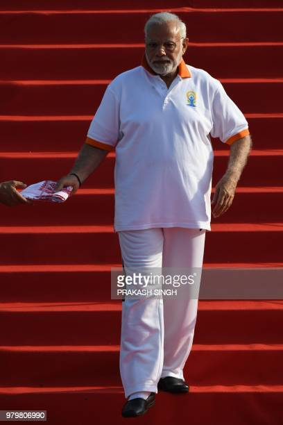 Indian Prime Minister Narendra Modi is handed a scarf as he walks down steps to participate in a mass yoga session along with other practitioners to...