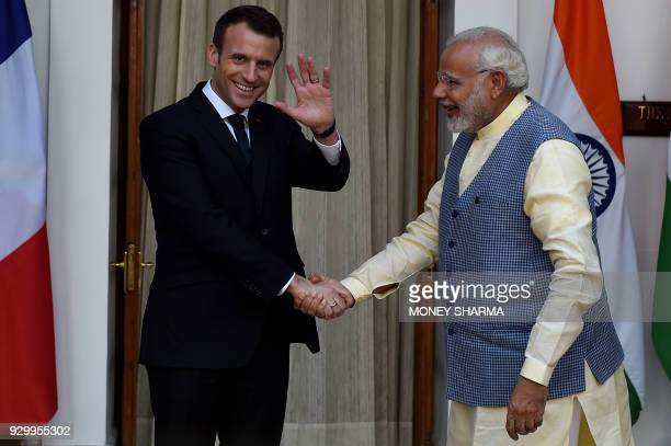 Indian Prime Minister Narendra Modi looks on as France's President Emmanuel Macron waves before a meeting at Hyderabad House in New Delhi on March 10...