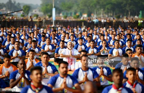 Indian Prime Minister Narendra Modi participates in a mass yoga session along with other practitioners to mark International Yoga Day at the Forest...