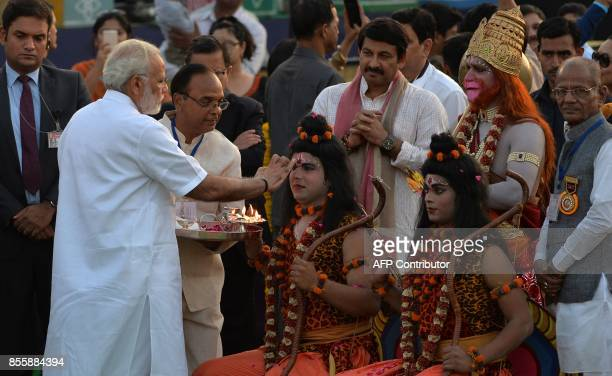Indian Prime Minister Narendra Modi performs a religious ritual with performers dressed as Hindu deities Rama and Lakshman ahead of the burning of...
