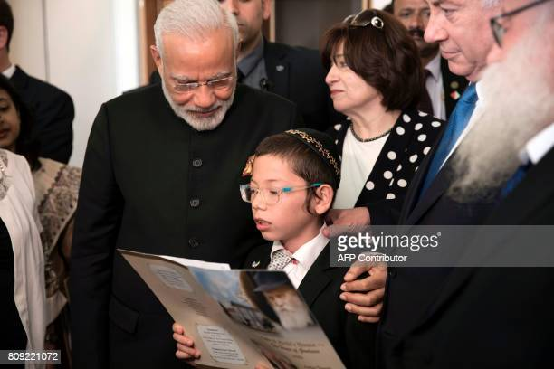 Indian Prime Minister Narendra Modi places his hand on the shoulder of Moshe Holtzberg son of slain US Rabbi Gavriel Holtzberg who was killed with...