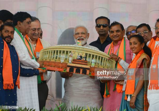 Indian Prime Minister Narendra Modi recieves a gift of a model cut-out of the Indian Parliament House during his rally in Amreli, some 250km from...