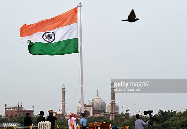 Indian Prime Minister Narendra Modi salutes as he unfurls the Indian national flag before delivering his Independence Day speech from The Red Fort in...