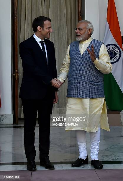 Indian Prime Minister Narendra Modi shakes hand with France's President Emmanuel Macron before a meeting at Hyderabad House in New Delhi on March 10...
