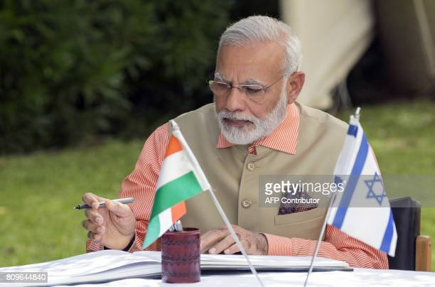 Indian Prime Minister Narendra Modi signs the guest book during a memorial ceremony at the Indian Army Cemetery of the World War I to honour fallen...