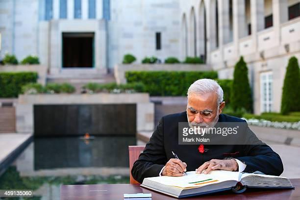 Indian Prime Minister Narendra Modi signs the visitors book at the Australian War Memorial on November 18, 2014 in Canberra, Australia. Prime...