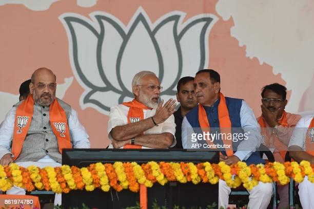 Indian Prime Minister Narendra Modi speaks to Gujarat State Chief Minister Vijaybhai Rupani in the presence of Bhartiya Janta Party President...