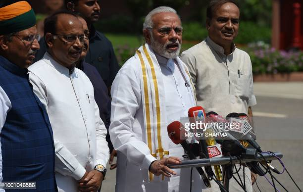 Indian Prime Minister Narendra Modi stands with senior Bharatiya Janata Party leaders as he addresses media representatives after arriving for the...