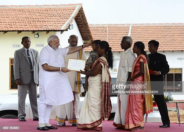 Indian Prime Minister Narendra Modi takes part in a ceremony as he handed over Indianfunded houses to Tamils displaced or made destitute by fighting...
