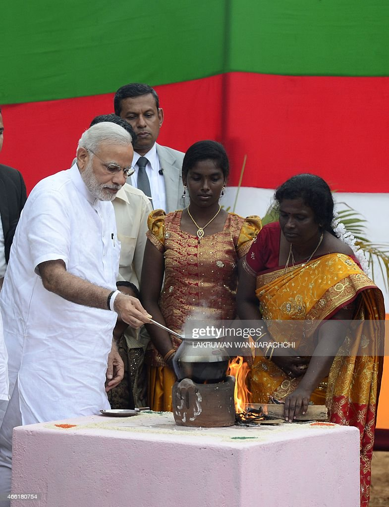 Indian Prime Minister Narendra Modi (L) takes part in a milk boiling ceremony as he handed over Indian-funded houses to Tamils displaced or made destitute by fighting in Jaffna, some 400 kilometres (250 miles) north of Colombo on March 14, 2015. Narendra Modi landed in Jaffna on March 14, becoming the first Indian prime minister to visit Sri Lanka's war-ravaged northern Tamil heartland. AFP PHOTO / Lakruwan WANNIARACHCHI