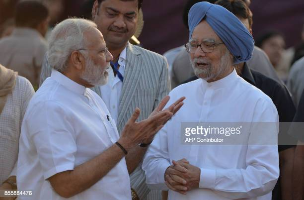 Indian Prime Minister Narendra Modi talks with former Indian prime minister Manmohan Singh ahead of the burning of the effigy of the Hindu demon...
