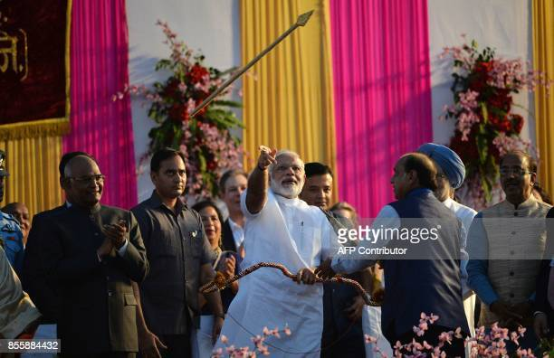 Indian Prime Minister Narendra Modi throws an arrow at an event ahead of the burning of the effigy of the Hindu demon Ravana at an event marking the...