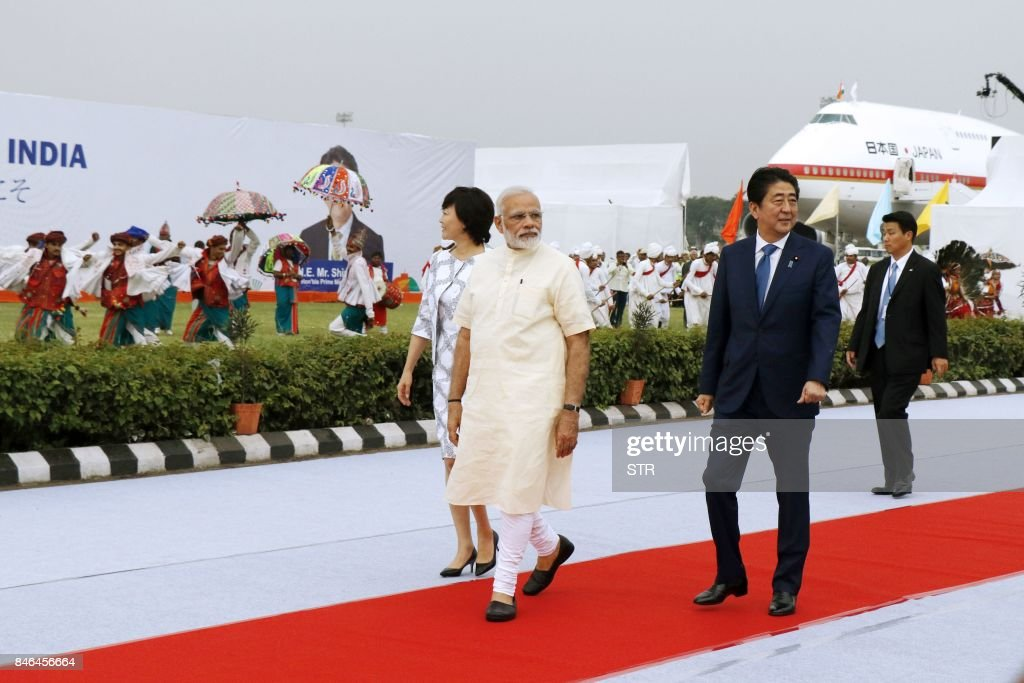 Indian Prime Minister Narendra Modi walks after welcoming Japanese Prime Minister Shinzo Abe (2R) and his wife Akie (L) upon their arrival at Ahmedabad's airport on September 13, 2017. As India's premier Modi and his Japanese counterpart Shinzo Abe prepare to break ground on the country's first bullet train project on September 14, experts say the collaboration could signal a massive leap for its overburdened and deadly railways. /