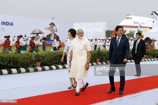 Indian Prime Minister Narendra Modi walks after welcoming Japanese Prime Minister Shinzo Abe and his wife Akie upon their arrival at Ahmedabad's...