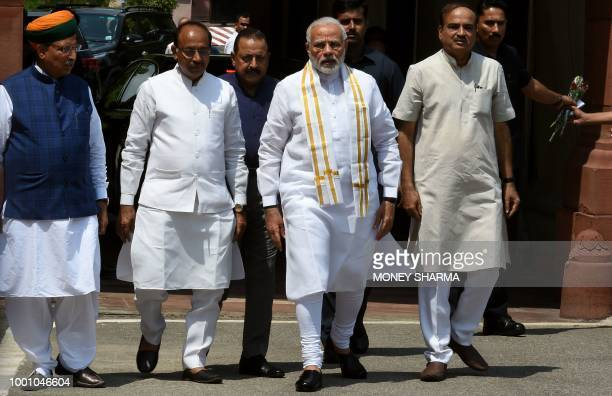 Indian Prime Minister Narendra Modi walks with senior Bharatiya Janata Party leaders after arriving for the monsoon session of Parliament in New...