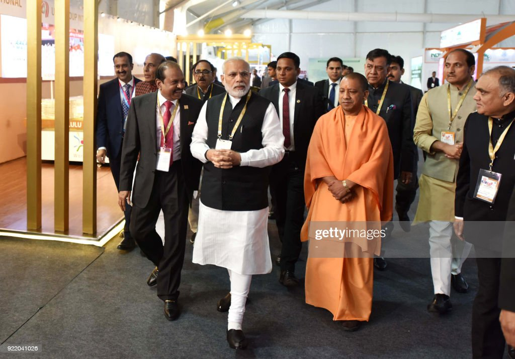 Indian Prime Minister Narendra Modi (C) walks with Uttar Pradesh (UP) Chief Minister Yogi Adiyanath (4R) during the inauguration of 'UP Investors Summit 2018' in Lucknow on February 21, 2018. The two-day summit which started on February 21 is aimed at showcasing investment opportunities and potential across various sectors in the northern Indian state of Uttar Pradesh. /