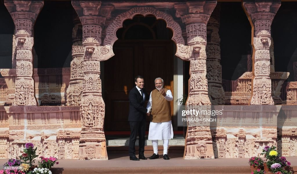 TOPSHOT - Indian Prime Minister Narendra Modi (R) welcomes French President Emmanuel Macron to the founding conference of the International Solar Alliance in New Delhi on March 11, 2018. The International Solar Alliance (ISA) organizes more than 121 'sunshine' countries that are situated or have territory between the Tropic of Cancer and the Tropic of Capricorn, with the aim of boosting solar energy output in an effort to reduce global dependence on fossil fuels. / AFP PHOTO / Prakash SINGH