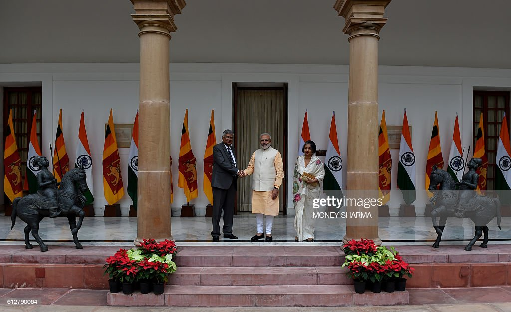 Indian Prime Minister Narendra Modi(C)shakes hands with Sri Lankan Prime Minister Ranil Wickremesinghe (L) as his wife Maithree Wickremesinghe (R) looks on before a meeting at Hyderabad House in New Delhi on October 5, 2016. / AFP / MONEY