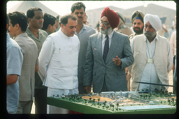 Indian Prime Minister Rajiv Gandhi looks at a plan for a new paper mill during his visit to the Punjab state September 21 1988 in Punjab India Sikhs..