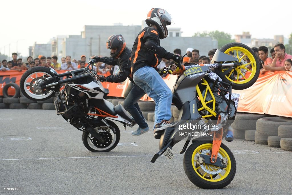 Indian professional stuntmen perform on motorbikes during the KTM stunt show in Amritsar on June 10 2018