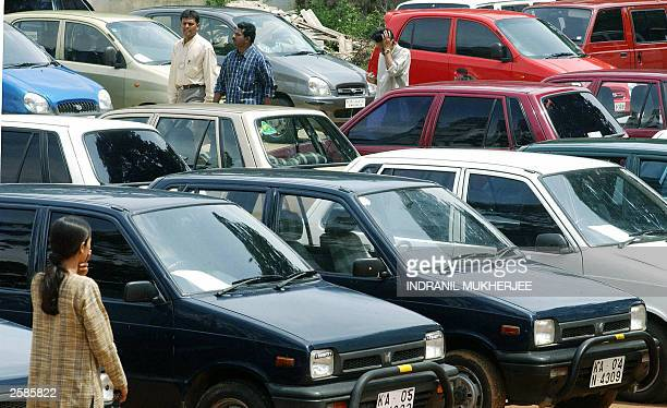 Indian prospective car buyers pause as they inspects cars at an used car market in Bangalore 12 October 2003 The Indian used car market which has...