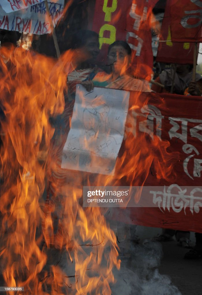 Indian protesters burn an effigy of Indian Prime Minister Manmohan Singh as they take part in a protest rally in Siliguri on December 29, 2012, after the death of a gangrape victim from the Indian capital New Delhi. Indian leaders appealed for calm and security forces headed off fresh unrest by turning New Delhi into a fortress after a student who was savagely gang-raped died in a Singapore hospital. Police threw a ring of steel around the centre of the Indian capital after news of the 23-year-old medical student's death was broken in the early hours by the Singapore hospital that had been treating her for the last two days. AFP PHOTO/Diptendu DUTTA