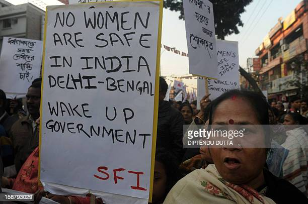 Indian protesters carry banners as they take part in a protest rally in Siliguri on December 29 after the death of a gangrape victim from the Indian...
