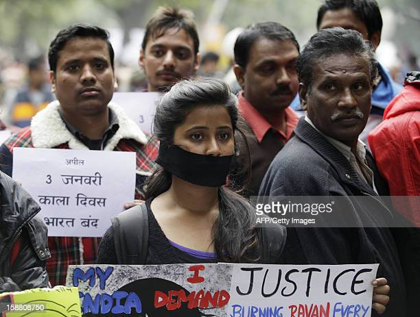 Indian protesters hold banners and wear black ribbons during a rally in New Delhi on December 30 following the cremation of a gangrape victim in the...