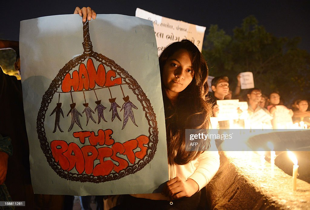 Indian protesters hold candles and posters during a rally in Ahmedabad on December 30, 2012, following following the cremation of a gangrape victim in the Indian capital. The victim of a gang-rape and murder which triggered an outpouring of grief and anger across India was cremated at a private ceremony, hours after her body was flown home from Singapore. A student of 23-year-old, the focus of nationwide protests since she was brutally attacked on a bus in New Delhi two weeks ago, was cremated away from the public glare at the request of her traumatised parents. AFP PHOTO / Sam PANTHAKY