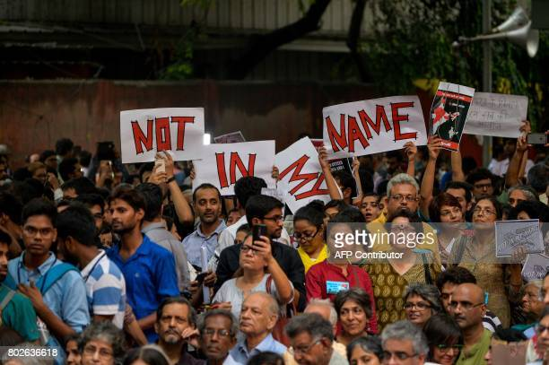 Indian protesters hold placards as they gather during a 'Not in my name' silent protest at Jantar Mantar in New Delhi on June 28 following a spate...