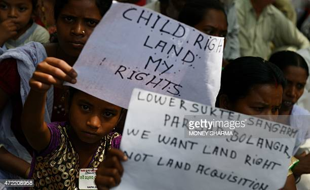Indian protestors are joined by children holding placards during a rally in New Delhi on May 5 against the ruling governments proposed land...