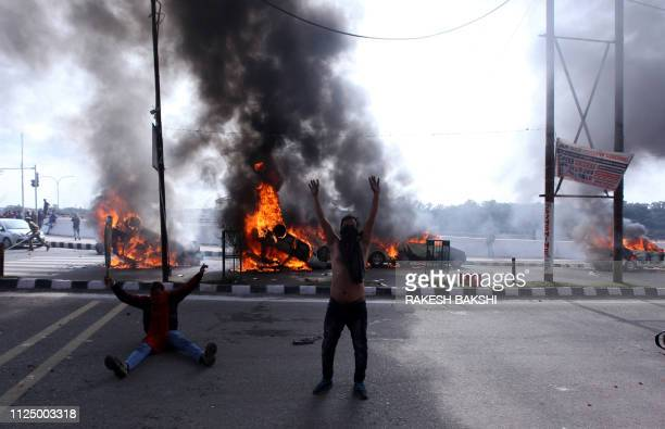 TOPSHOT Indian protestors shout slogans against Pakistan next to burning vehicles during a protest in Jammu on February 15 the day after an attack on...