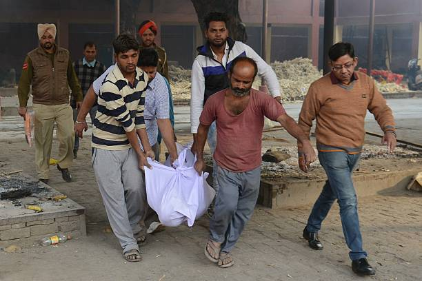 Indian Punjab police personnel along with social worker BK Sharma carry the dead body of an unidentified person at a cremation ground in Amritsar on..