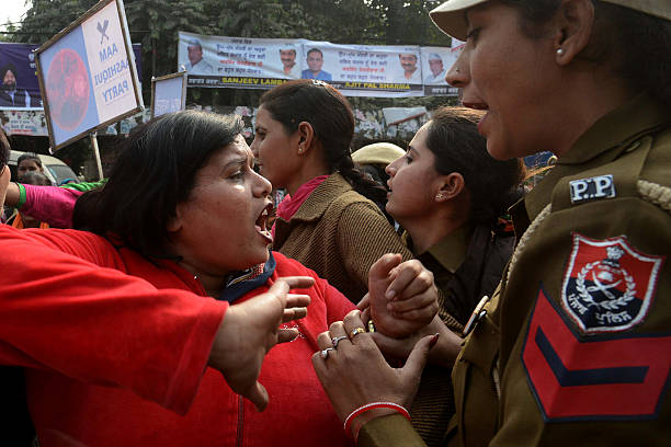 Indian Punjab police personnel force back activists from the Congress party shouting slogans against Delhi state chief minister Arvind Kejriwal as...