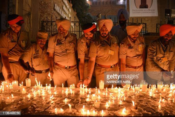 TOPSHOT Indian Punjab Police personnel light candles as they pay tribute to the Jallianwala Bagh massacre martyrs on the eve of the 100th anniversary...