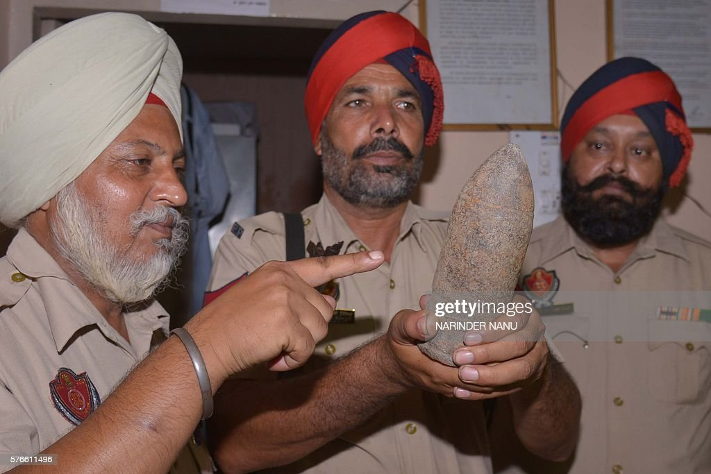 Indian Punjab Police personnel pose with used bomb shell which they found near an Army Cantonement area in Amritsar on July 16 2016 Punjab police...