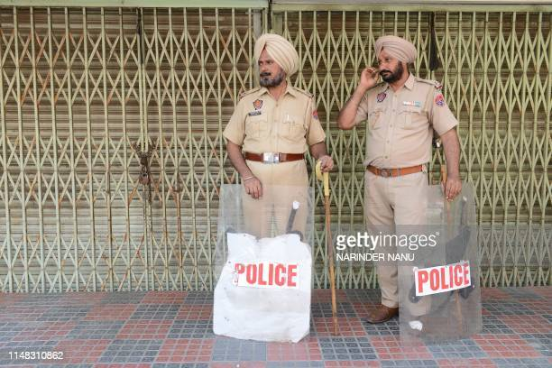Indian Punjab Police personnel stand guard outside shuttered shops during a strike call by Dal Khalsa, a Sikh radical organisation, on the occasion...