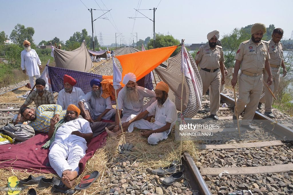 Indian Punjab police personnel walk past as farmers block train tracks during the second day of protest against the central and state governments at..
