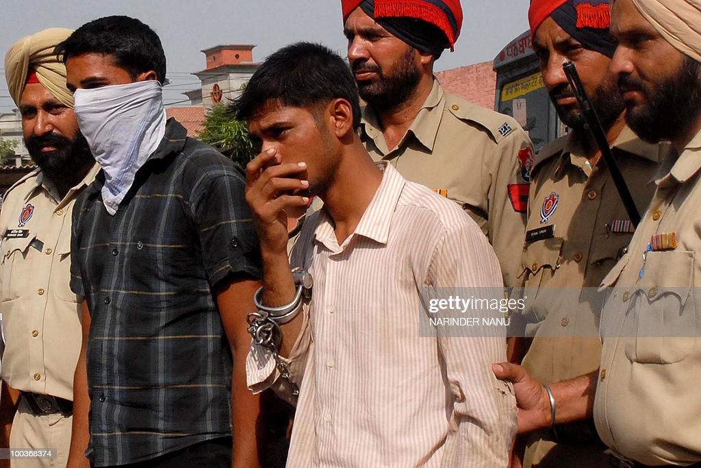 Indian Punjab Police personnel�s escort suspected smugglers Gagandeep Singh (2nd L) and Sardool Singh (3rd R) for an appearance in court at Tran Taran, about 25 kms from Amritsar, on May 24, 2010. Officials recovered some 22 kg of heroin believed to have been smuggled into the country from neighbouring Pakistan.