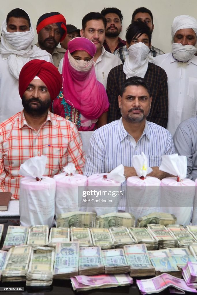 Indian Punjab police Special Task Force officers pose with 6 kg of heroin and 71000 rupees recovered from alleged smugglers Krishna Kumari Harmesh...