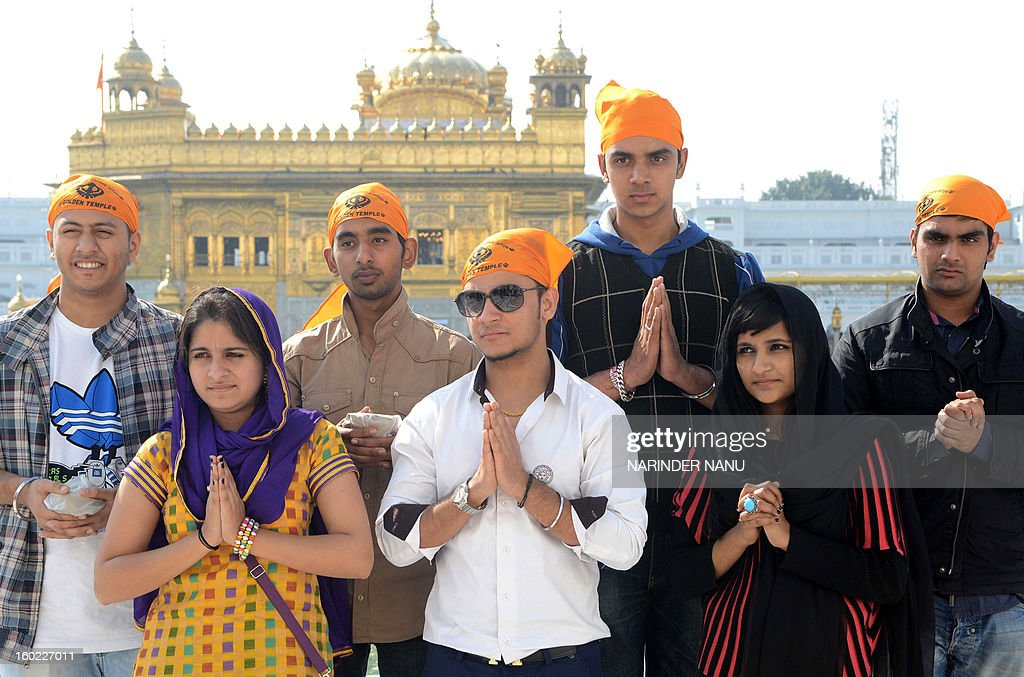 Indian Punjabi actor Millind Gaba (C), Saibi Sodhi (3R), Karanjit Singh (2L), Pukhraj Bhalla (L), actresses Jasmeet kaur(L), and Gunit Cour (2R) pose for a photo near the Golden temple in Amritsar on January 28, 2013. The actors visited the city as part of a promotional tour of their upcoming film 'Stupid 7' directed by Pali Bhupinder Singh.