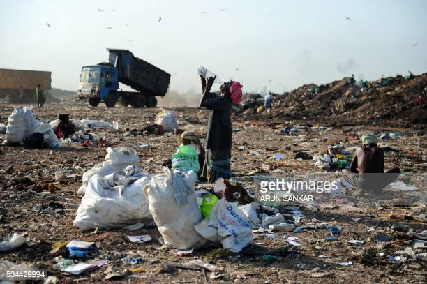 Indian ragpicker Chellammal drinks water as she collects usable items in garbage at a dumping yard on the outskirts of Chennai on May 26 2016...