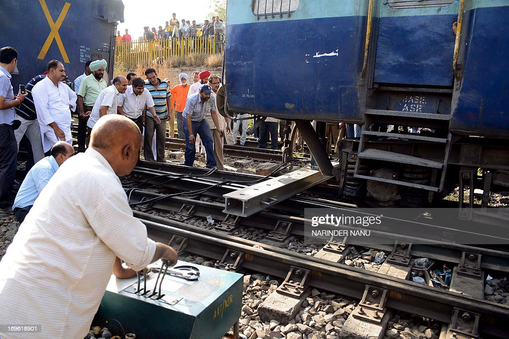 Indian railway employees with the help of machinery try to restore two coaches of a vacant train which were derailed while being taken for...