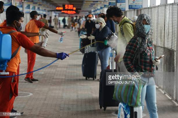Indian railway workers spray disinfectant to the luggages of passengers upon arriving from New Delhi at New Jalpaiguri railway station after the...