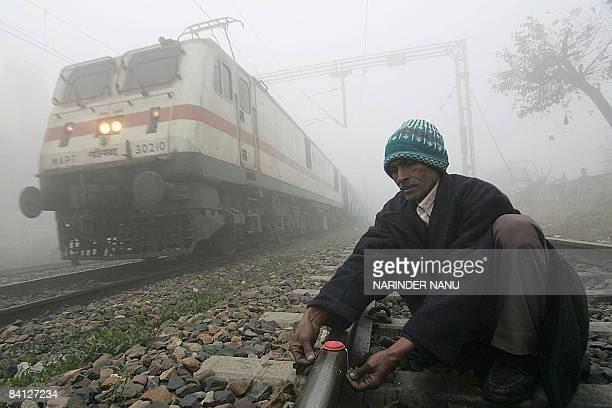 Indian Railways employee Prem Chand places a visibility marker on a railroad track as a train passes by in dense fog at the Amritsar Railway Station...
