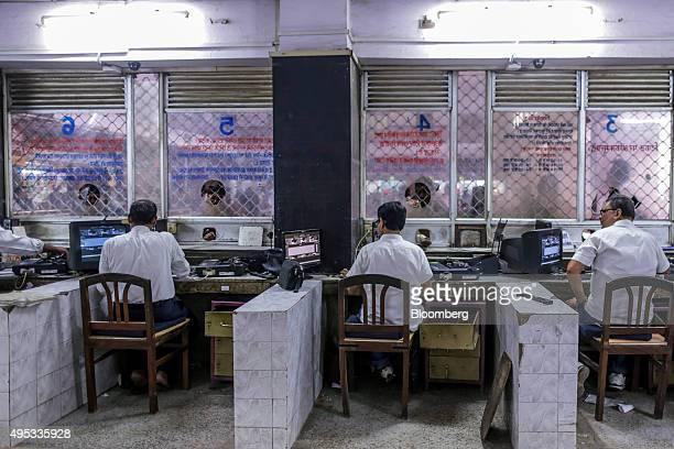 Indian Railways employees serve customers at a ticket office in Mughalsarai Junction station in Mughalsarai Uttar Pradesh India on Thursday Oct 1...