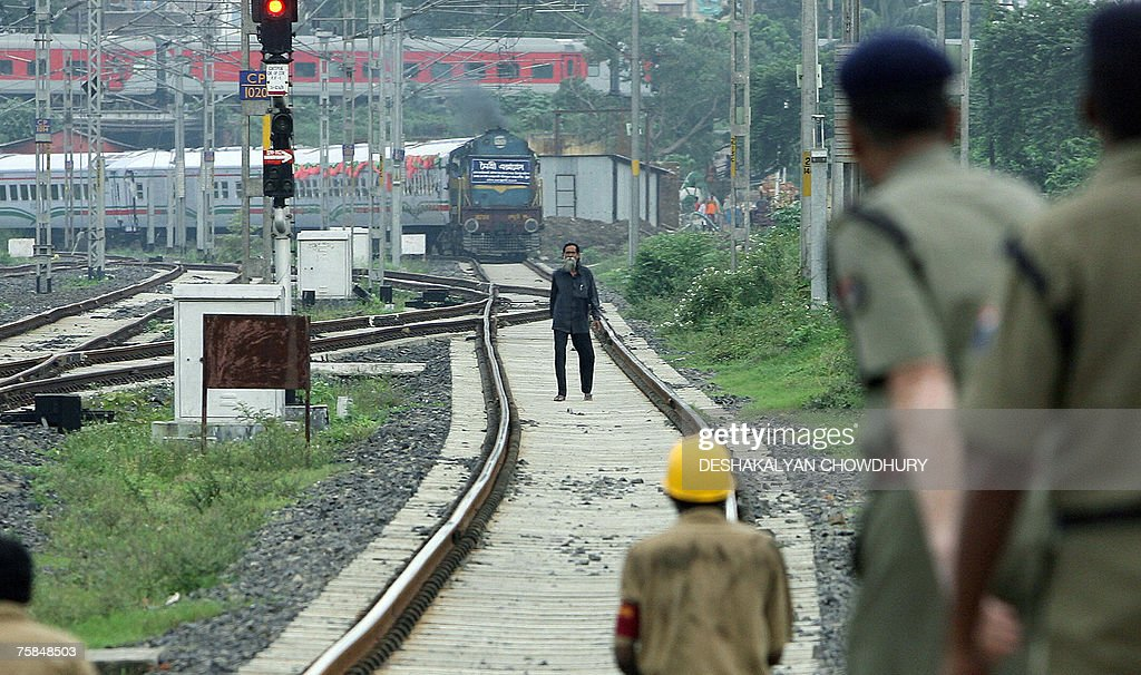 Indian railways police shout at an unidentified man